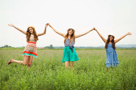 non cultivated: Happy girls smiling in wheat field Stock Photo