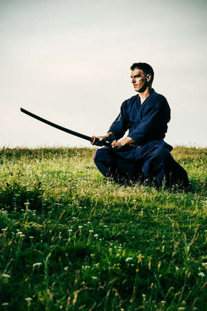 combative sport: Kendo fighter holding bokuto, intentionally toned. Stock Photo