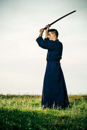 intentionally: Kendo fighter holding bokuto, intentionally toned. Stock Photo