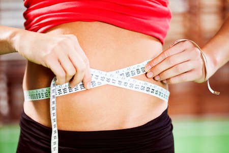 woman measuring waist: Woman measuring waist volume after exercising in gym Stock Photo