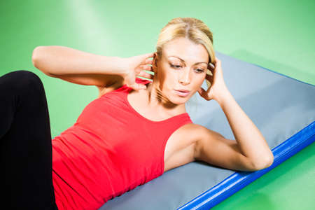 crunches: Young woman exercising in gym, doing crunches