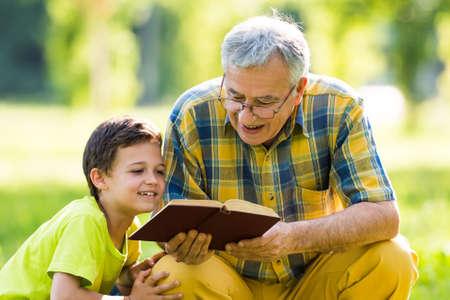 ni�os leyendo: Abuelo y nieto aprender sobre la naturaleza Foto de archivo