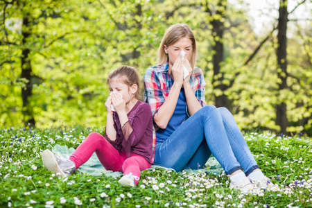 Two people with allergy symptom blow their noses Stock Photo