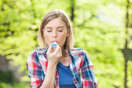asma: Mujer con asma usando el inhalador  Foto de archivo