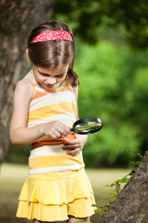 exploring: Little girl exploring nature with loupe Stock Photo