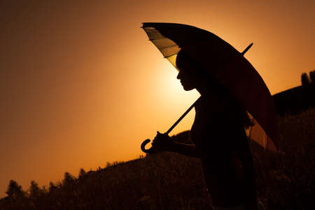 Silhouette of woman with umbrella at sunset photo