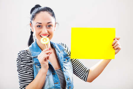 finger licking: Woman holding yellow paper with blank space for text message