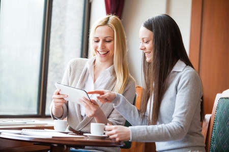 Two women drinking coffee and using digital tablet in cafe
