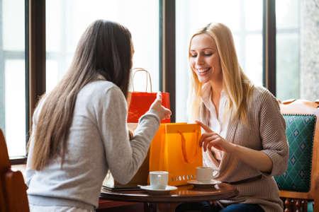 周囲の光で撮影した写真のショッピングの後カフェで話している 2 人の女性