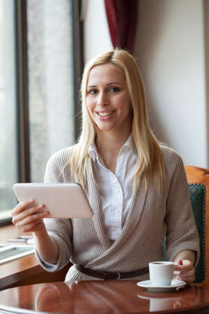 ambient light: Happy young woman using digital tablet in cafe, photo taken with ambient light