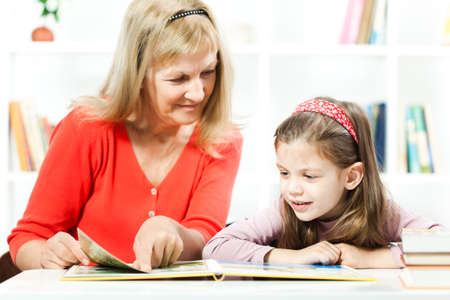 Happy child reading a book with help of her grandmother