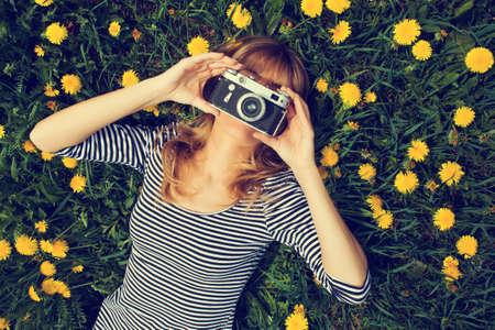 女の子の芝生で横になっていると写真を撮るします。意図的にトーンダウン。