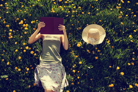 Girl lying in grass reading a book. Intentionally toned. Stockfoto
