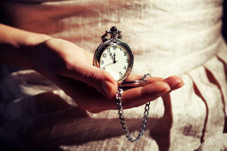 Woman holding antique watch that shows five to twelve time intentionally toned.