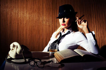 intentionally: Retro styled businesswoman smoking cigar and drinking whiskey intentionally toned. Stock Photo