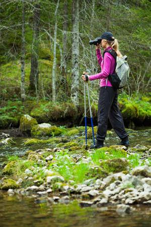 outdoor pursuit: Hiker looking through binoculars in forest