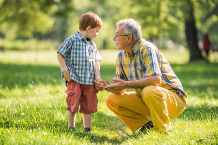 Grandfather and grandson are talking in park Imagens