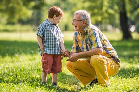 할아버지와 손자가 공원에서 이야기하고있다. 스톡 콘텐츠
