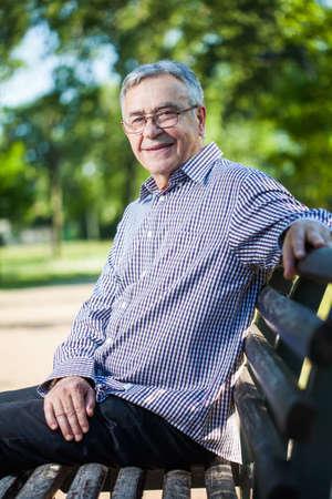 Happy senior man sitting on bench in park