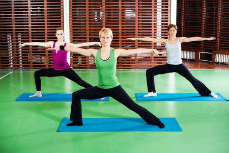 virabhadrasana: Girls practicing yoga Virabhadrasana  Warrior pose Stock Photo