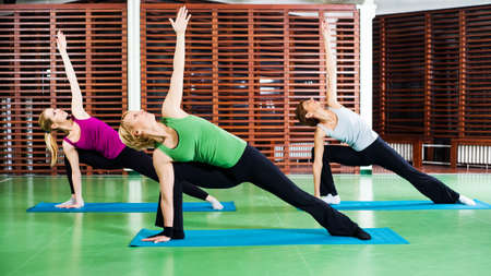 woman pose: Girls practicing yoga Bikram triangle right pose