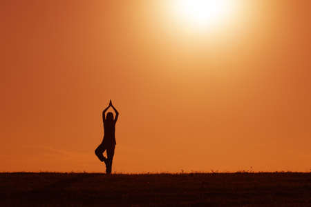 Silhouette of woman meditating in the sunset photo