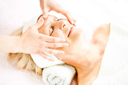 mature people: Mature woman having forehead massage