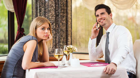 Woman is bored at restaurant, her boyfriend talks on the phone
