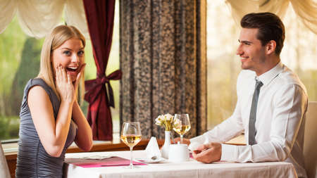 Happy couple at restaurant, man is proposing his girlfriend