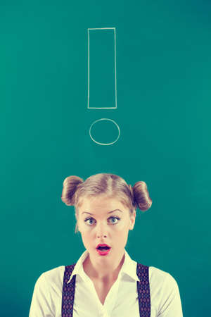 intentionally: Student girl in front of blackboard with an exclamation mark, intentionally toned. Stock Photo