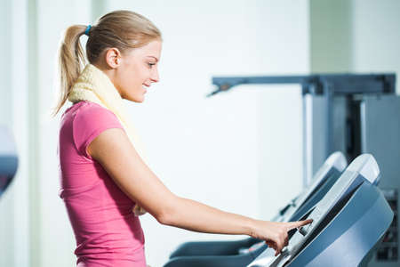 moving activity: Happy woman adjusts treadmill in gym