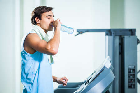 man drinking water: Man drinking water while exercising in gym Stock Photo