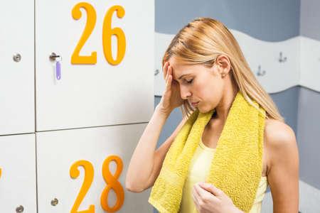 locker room: Tired girl in locker room after fitness training Stock Photo