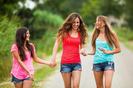 niñas sonriendo: Tres muchachas felices están caminando en la calle y hablar