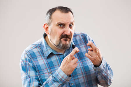 raised eyebrows: Portrait of man with fingers crossed