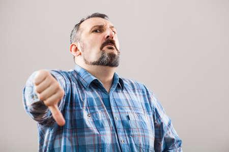 pulgar abajo: Retrato del hombre que muestra el pulgar hacia abajo Foto de archivo