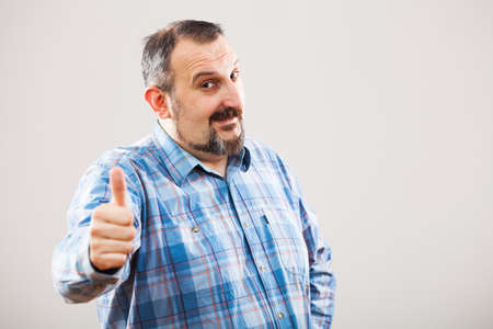 raised eyebrows: Portrait of man showing thumb up