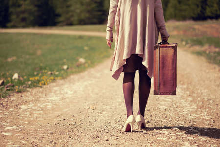 intentionally: Woman walking on country road with old suitcase, intentionally toned.
