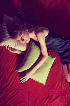 intentionally: Young woman sleeping lonely in bed, intentionally toned.