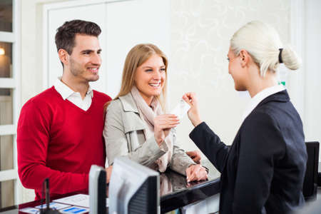 customer service representative: Young couple check in at hotel reception