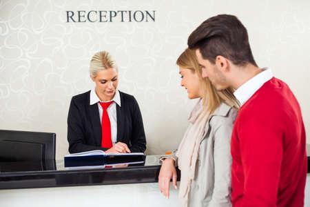 若いカップルは、ホテルのフロントでチェックインします。