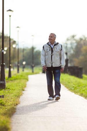 Happy senior man walking on the promenade