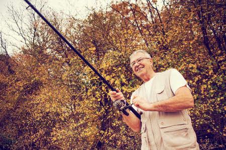 intentionally: Happy senior man fishing, intentionally toned.