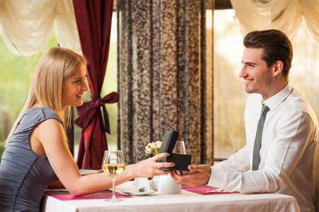 Happy couple at the restaurant, girl is giving present to her boyfriend Foto de archivo