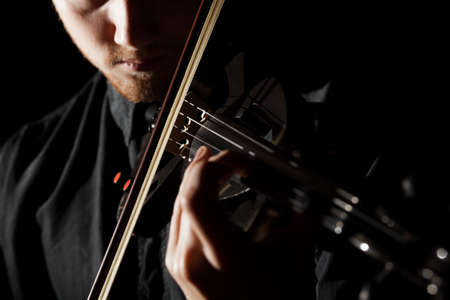 violin background: Close-up photo of man playing electric violin Stock Photo