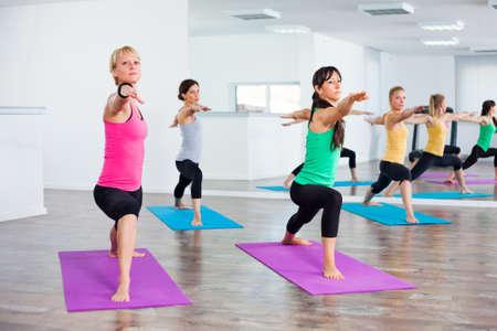 Four girls practicing yoga, Yoga Virabhadrasana Warrior pose Фото со стока