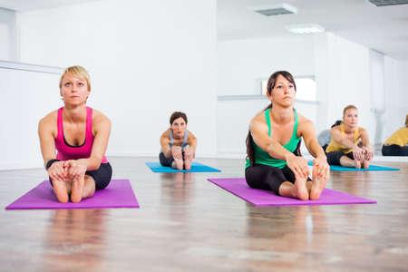 relaxation exercise: Four girls practicing yoga, Pascimottanasana Seated Forward Bend pose
