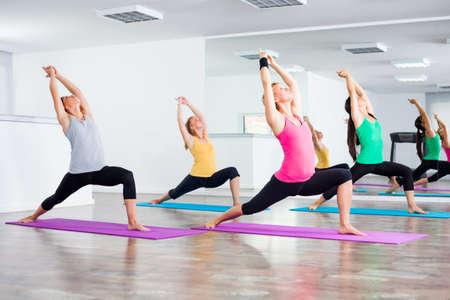 Four girls practicing yoga, Yoga - VirabhadrasanaWarrior pose