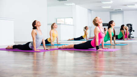 Four girls practicing yoga, Yoga Bhujangasana Cobra Pose
