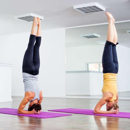 headstand: Two girls practicing yoga, Yoga Sirsasana Headstand Stock Photo